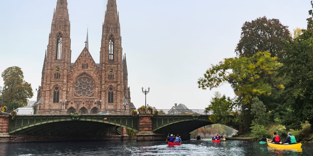 The Gothic-style Saint Paul Temple Church with tall pointed spires along the bank of the Rhine River