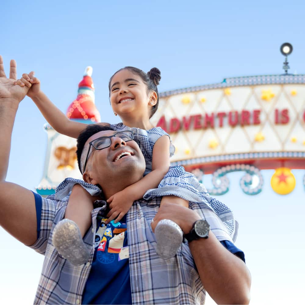 A smiling girl holds her father's hand while on his shoulders in front of a sign that reads
