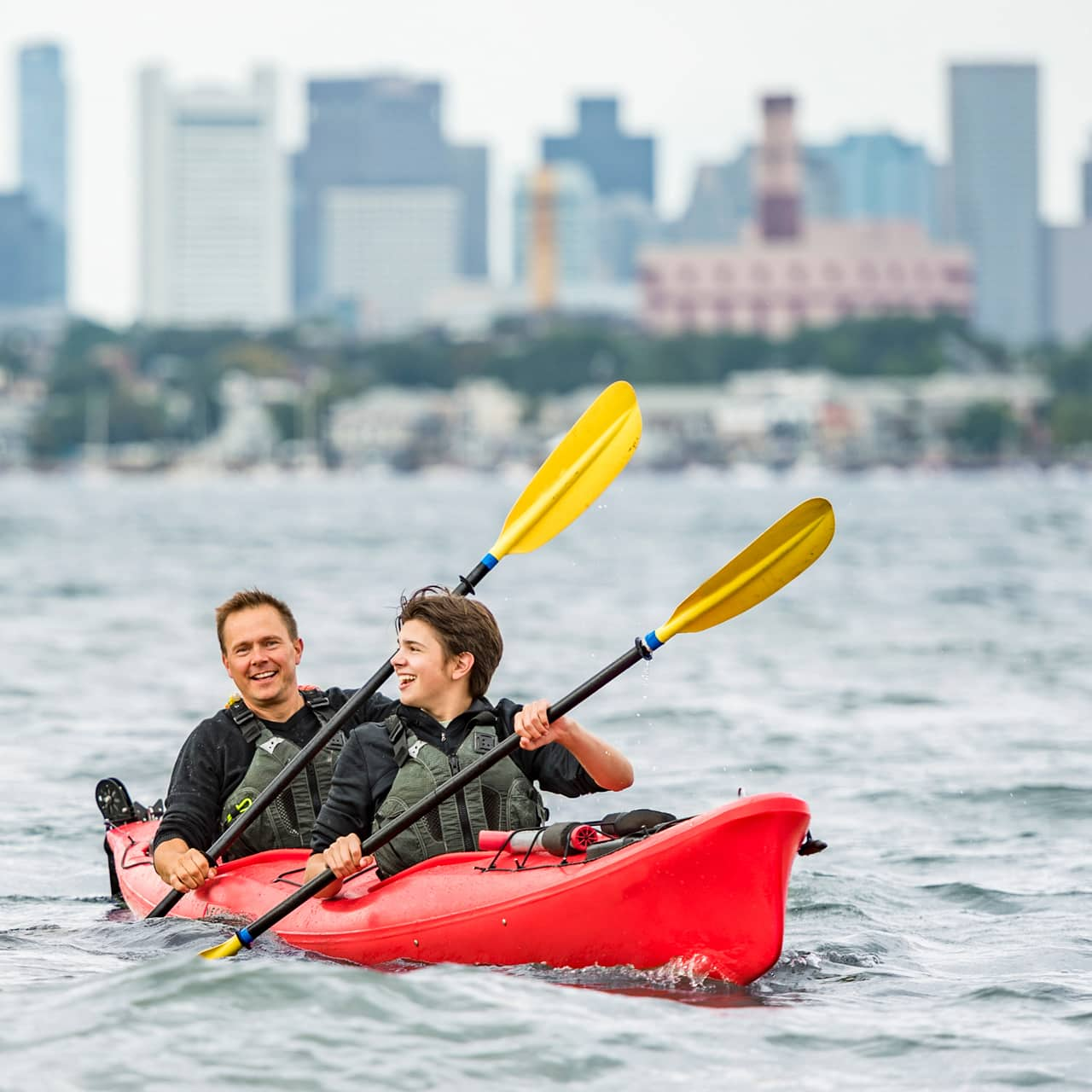 Two Adventurers in kayaks row in the water with the Boston skyline in the background