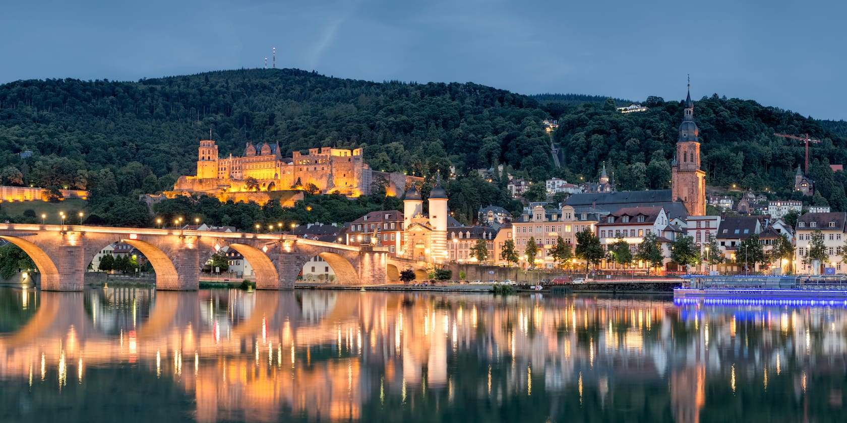 Heildelberg Castle stands between a tree-lined mountain and and a stone bridge, which is reflected in the Rhine River