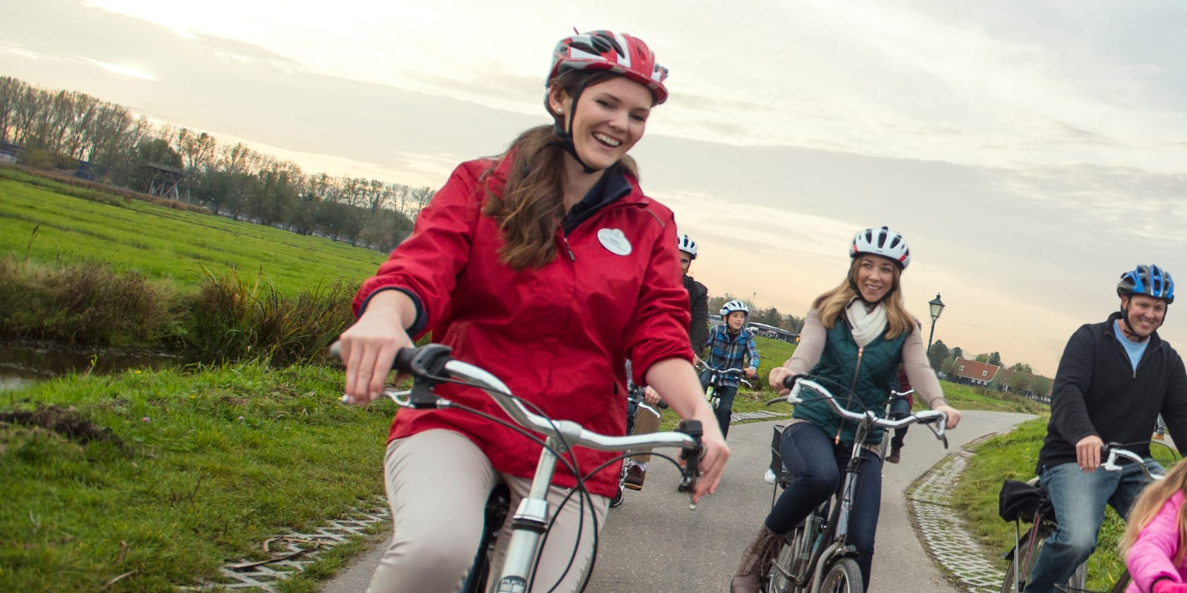 A female Adventure Guide and several Guests wearing helmets, bike along a path in Rüdesheim