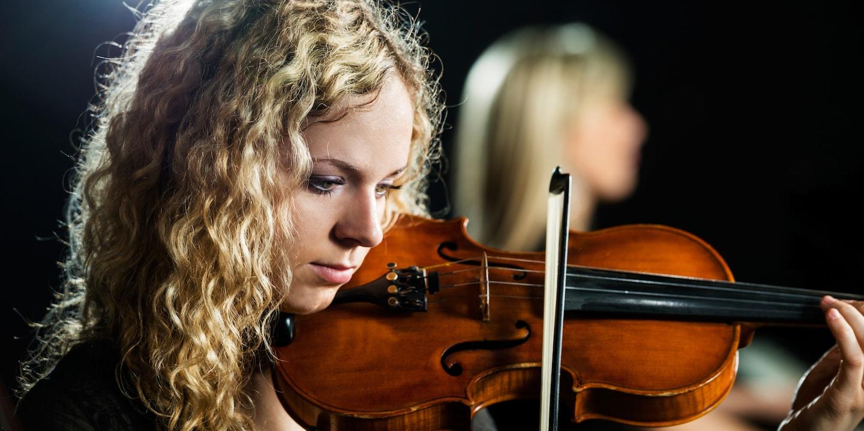 A pretty teenage girl plays a violin