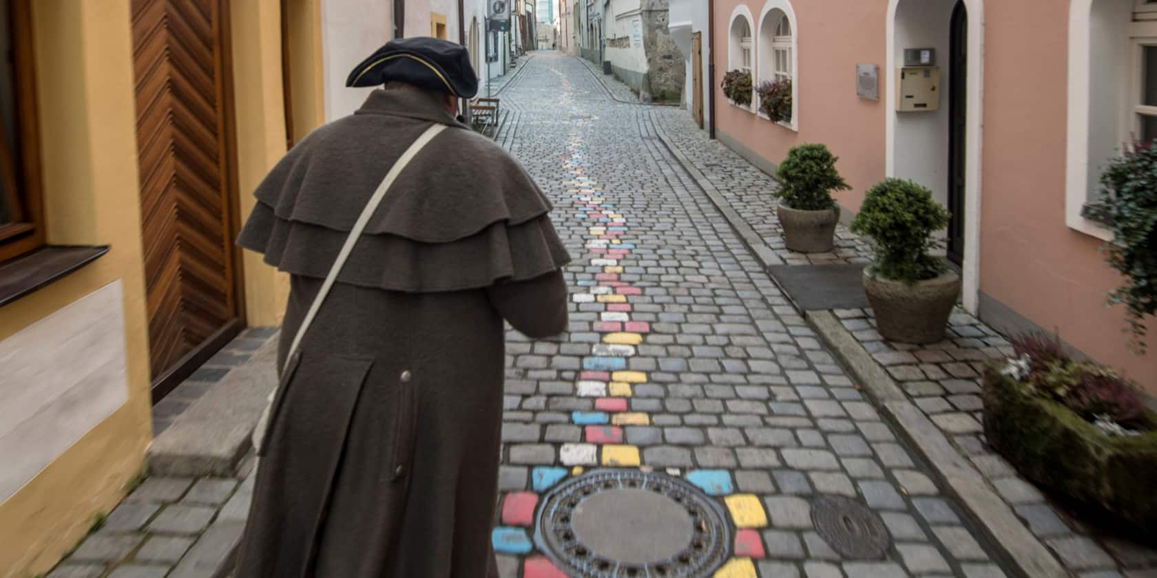 A man in a hat walks down a narrow, cobblestone street