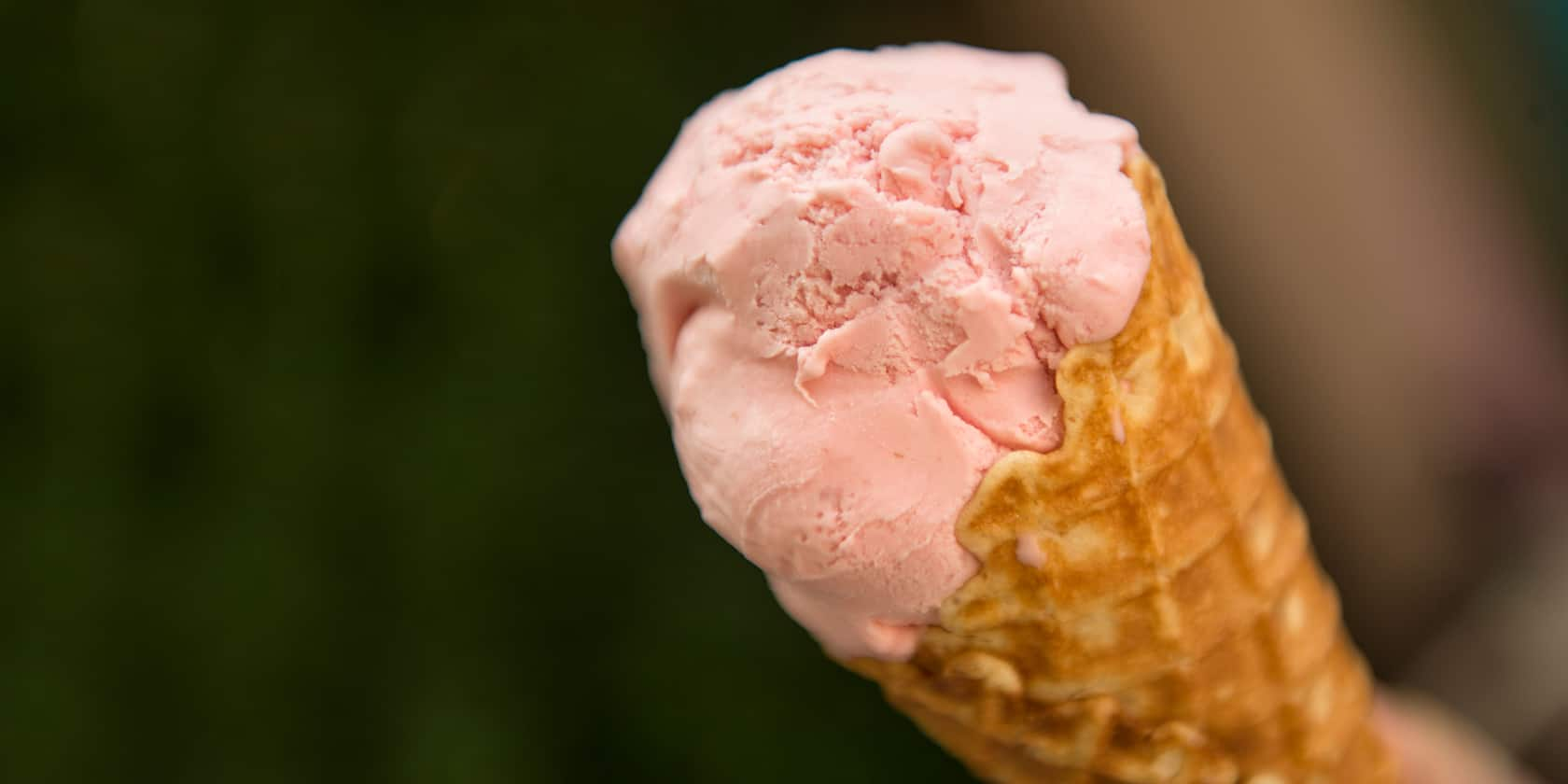 A scoop of strawberry ice cream inside a waffle cone