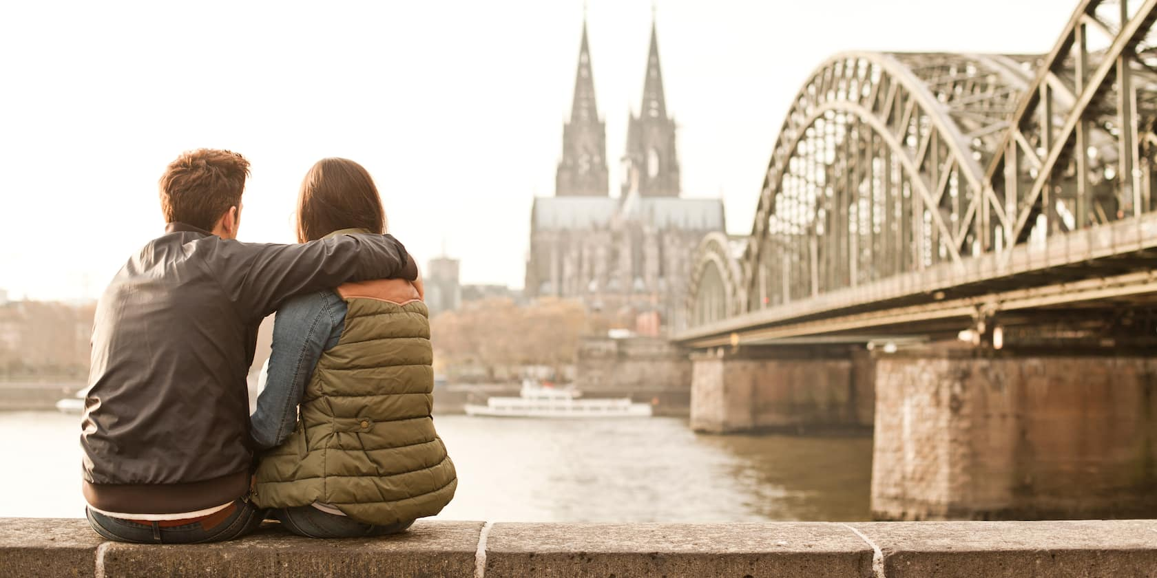 A couple sit on a bench looking out over the Rhine with the Cologne Cathedral in the background