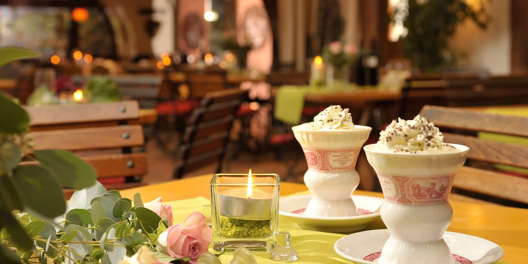 Two cups, topped with whipped cream, sit on a table with a lit candle and several roses in a restaurant with wood slatted chairs