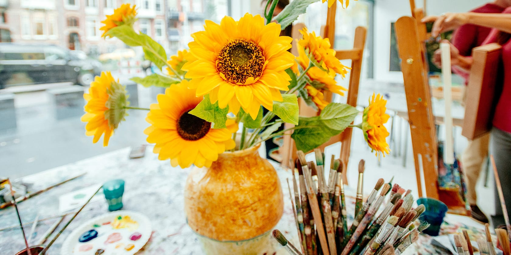 A vase filled with beautiful sunflowers sits on a table near a cup full of paint brushes, paints and other art supplies
