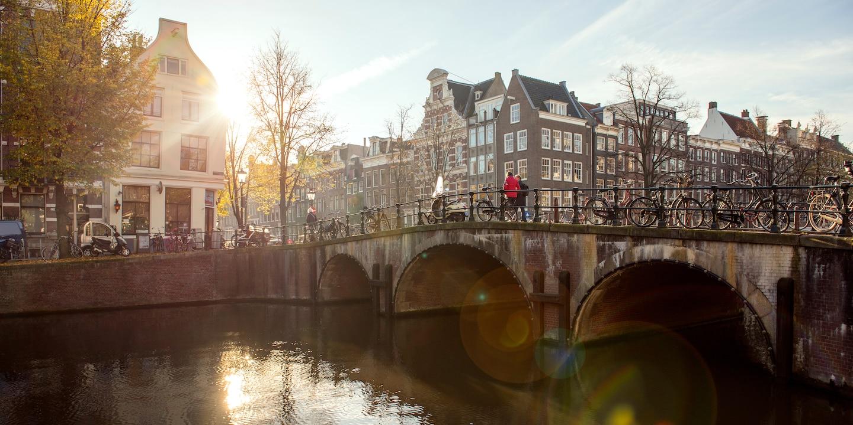A stone bridge over a river leads to a quaint European village