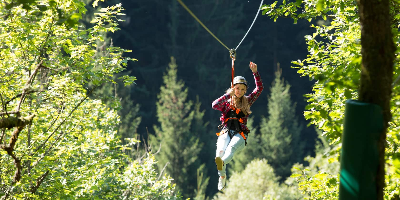 A girl waves as she ziplines through a forest