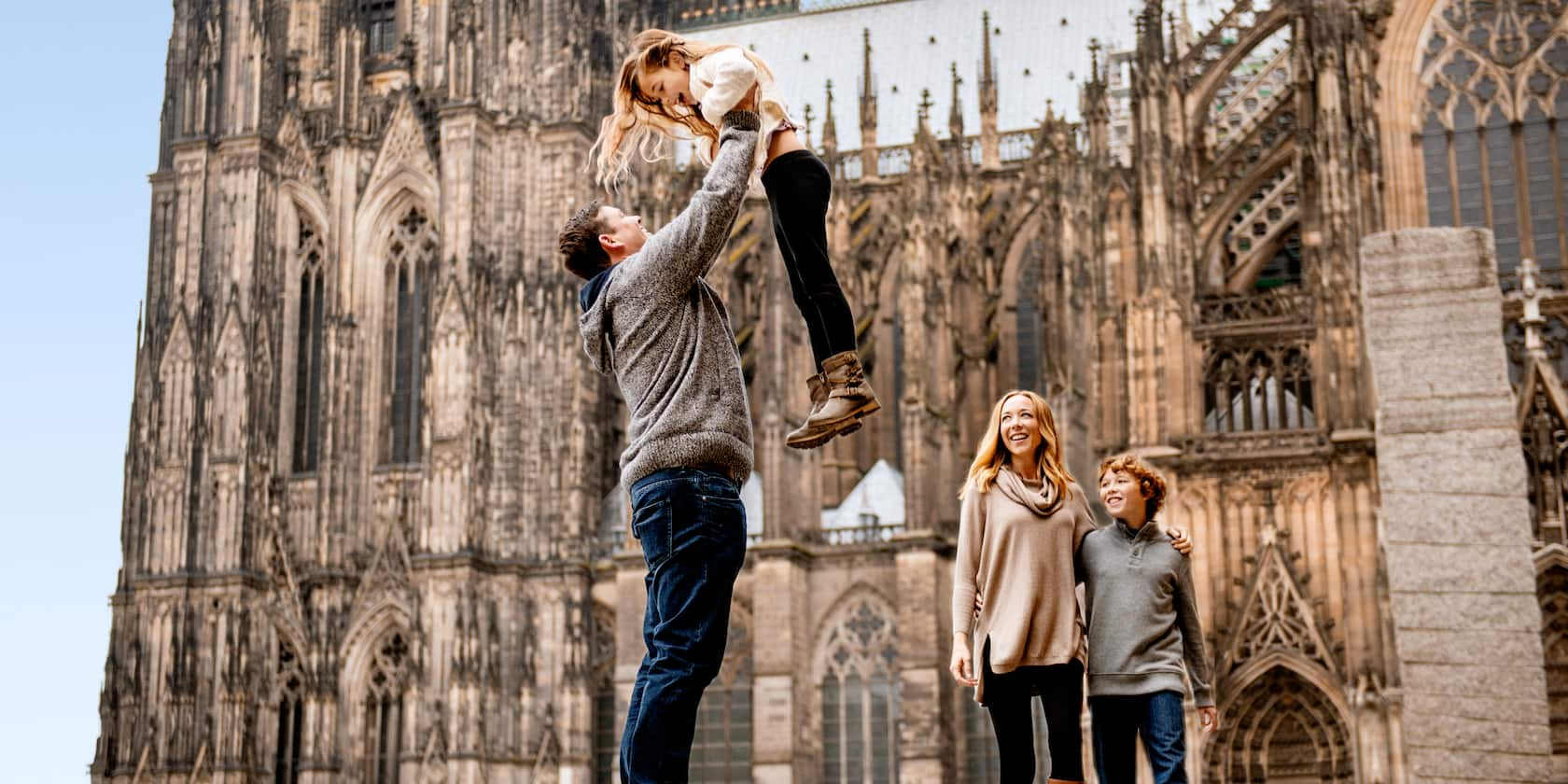 A father lifts his daughter up high in front of the Cologne Cathedral as his wife and son watch