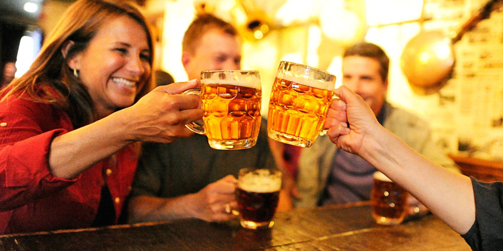 Two couples drinking beer in steins, with a woman toasting another woman