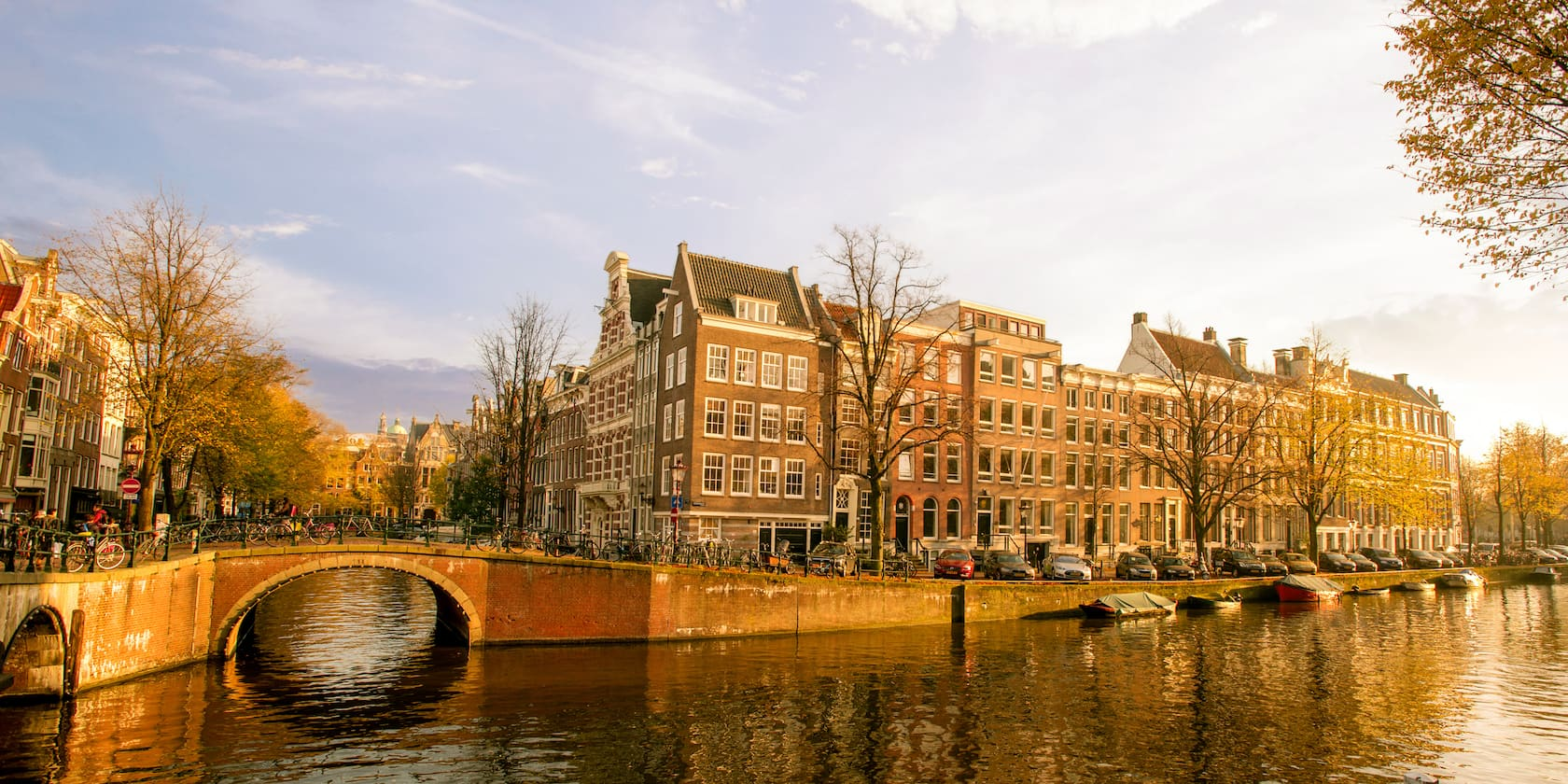 A stone bridge lined with bulidings spans a canal in Amsterdam