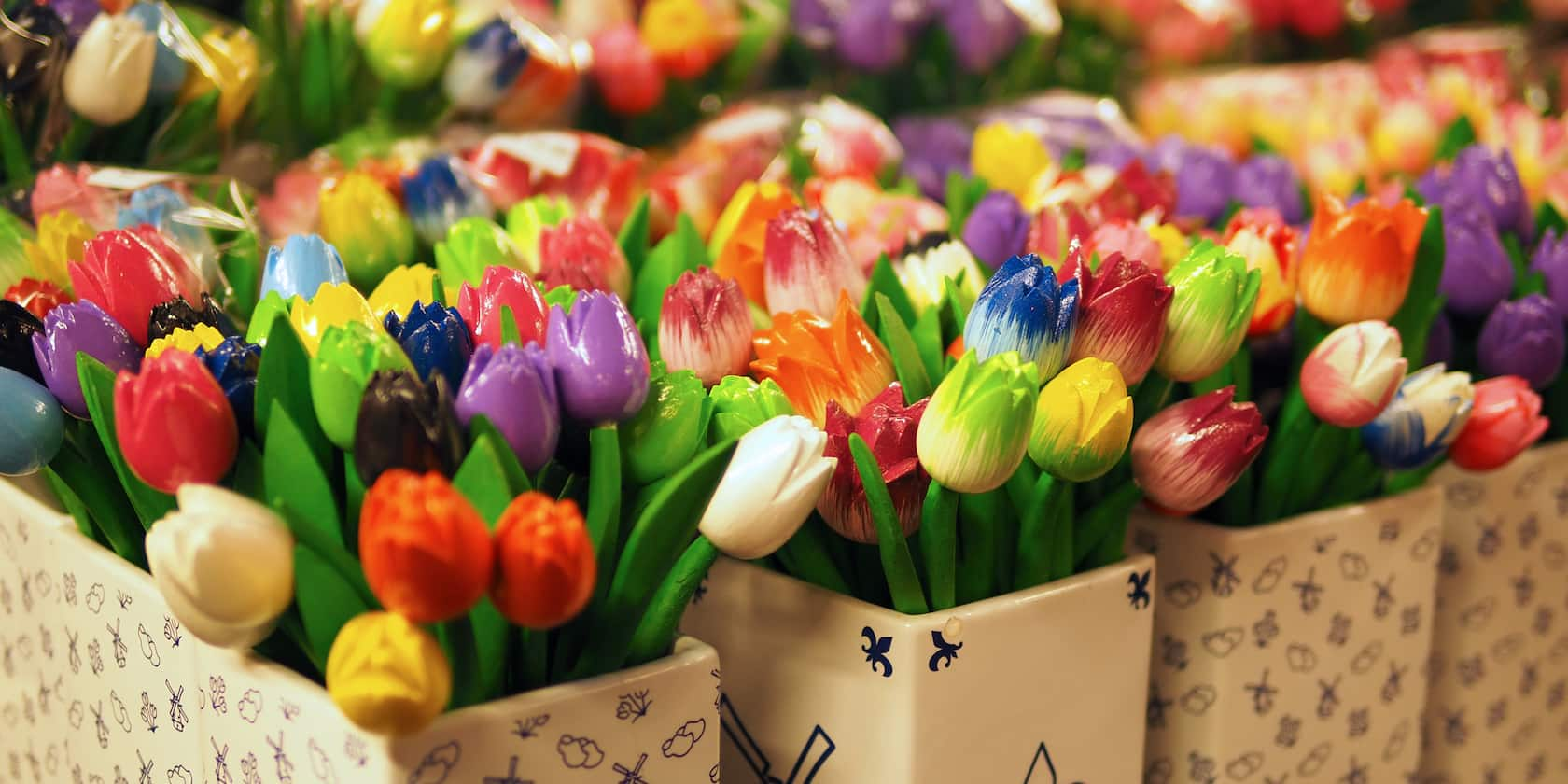 Several rows of ceramic vases filled with colorful artificial tulips