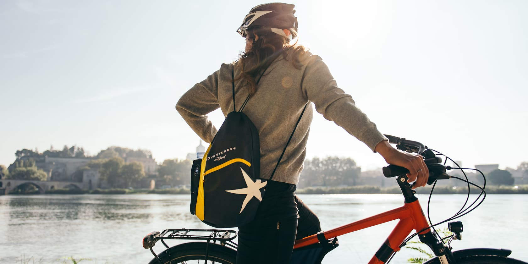 An Adventurer wearing an Adventures by Disney sack sits on a bicycle and looks out at the Rhône River