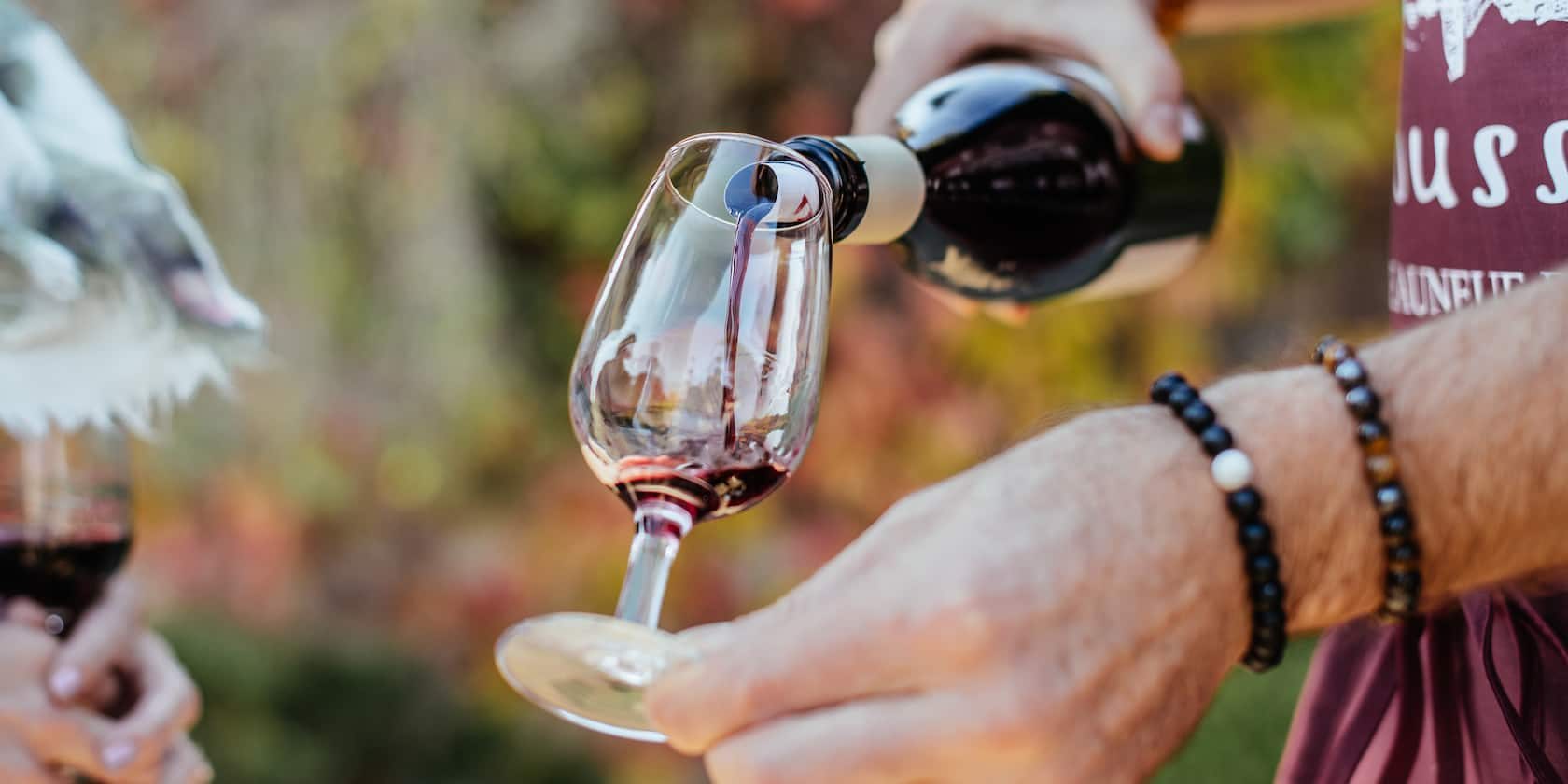 A man wearing beaded bracelets pours a glass of wine from a wine bottle
