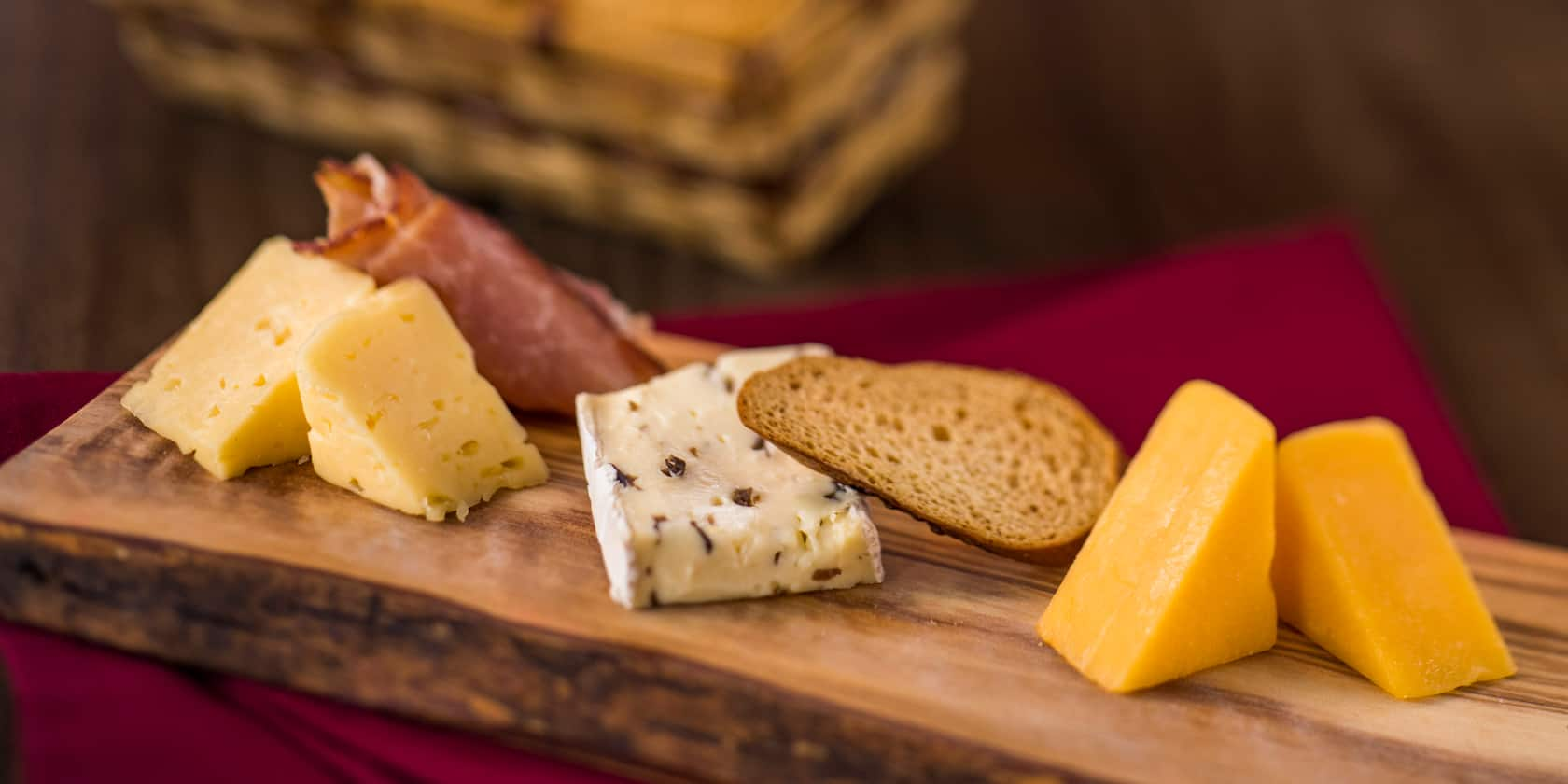 A selection of cheeses and crackers displayed on a wooden board
