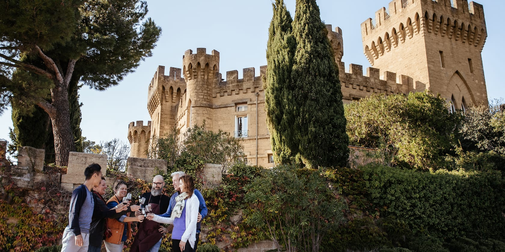 A group of people make a toast with wine glasses in front of Château des Fines Roches in Avignon, France
