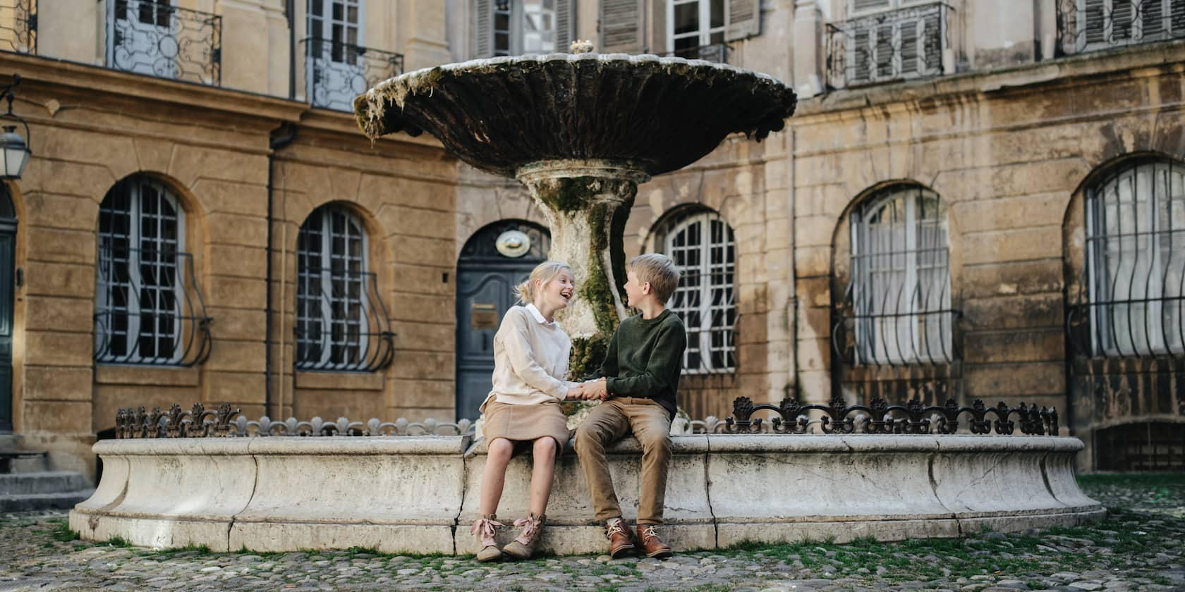 A young boy and girl sit on a fountain in a courtyard holding hands