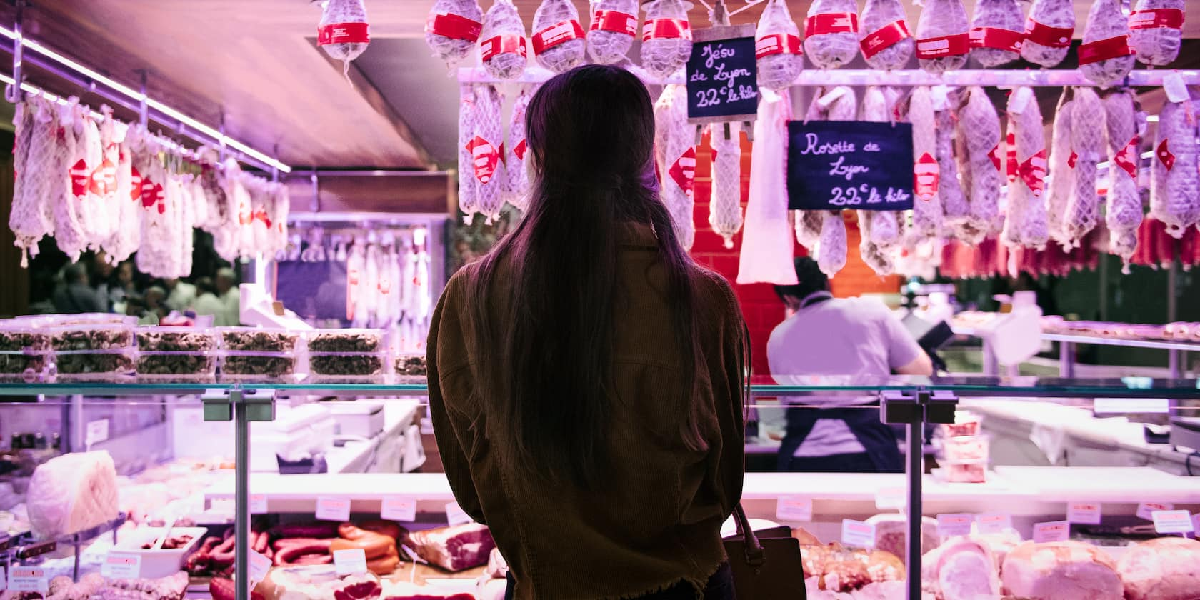 A woman looks at the display in a food stand at Les Halles market