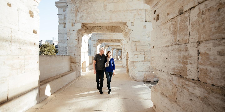 A man and woman walk through a hallway in a roman ruin in Arles, France
