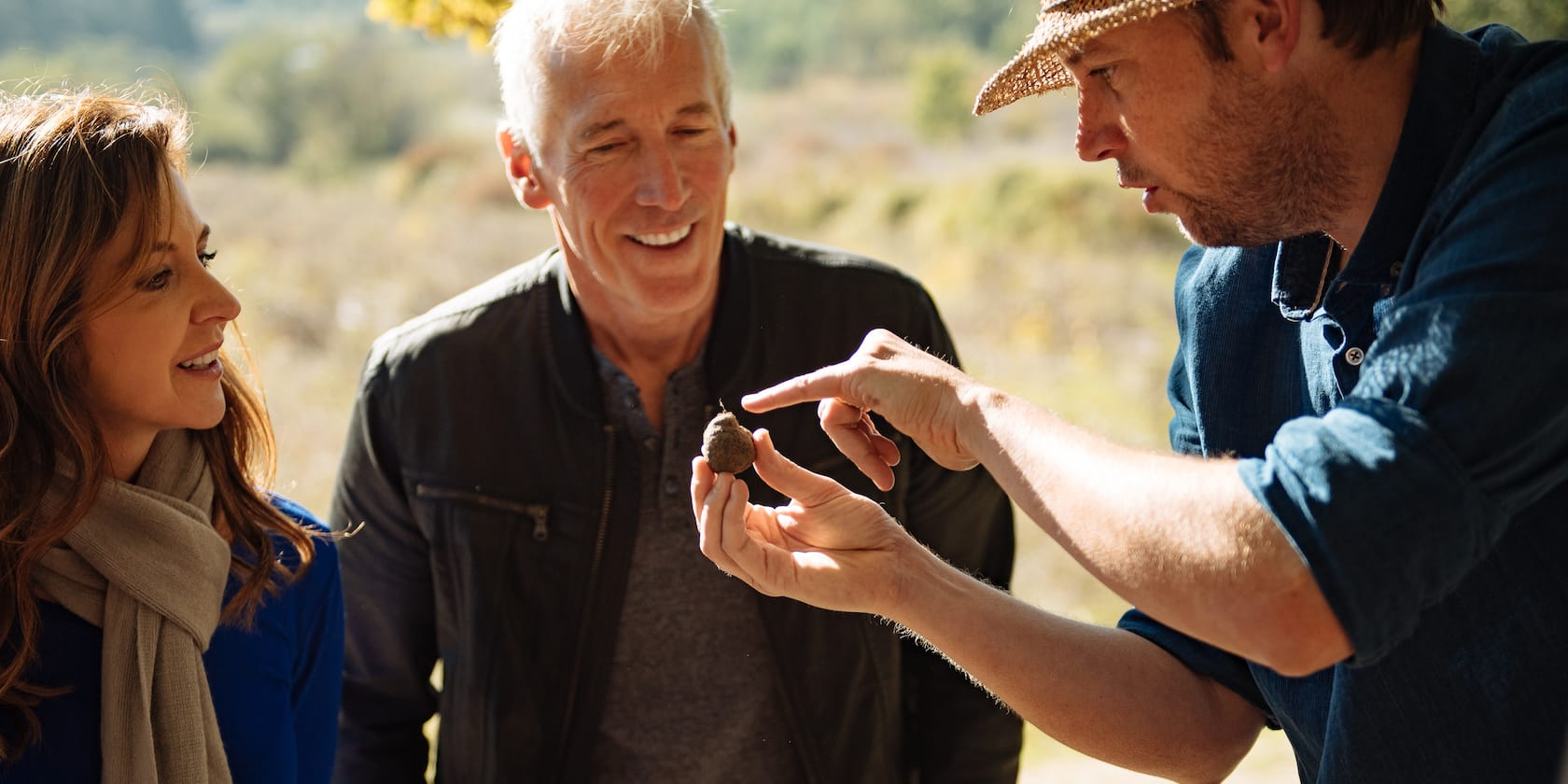 A man in a hat points out a truffle he is holding to a man and woman