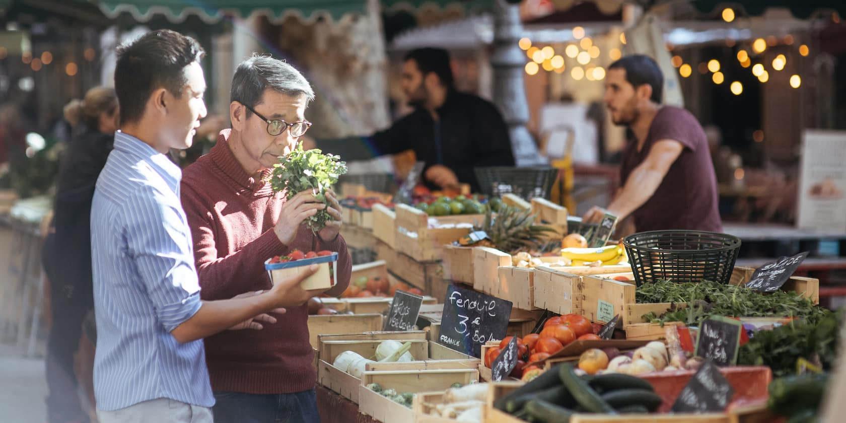 Two men check out the produce at an open-air market in Aix-en-Provence.