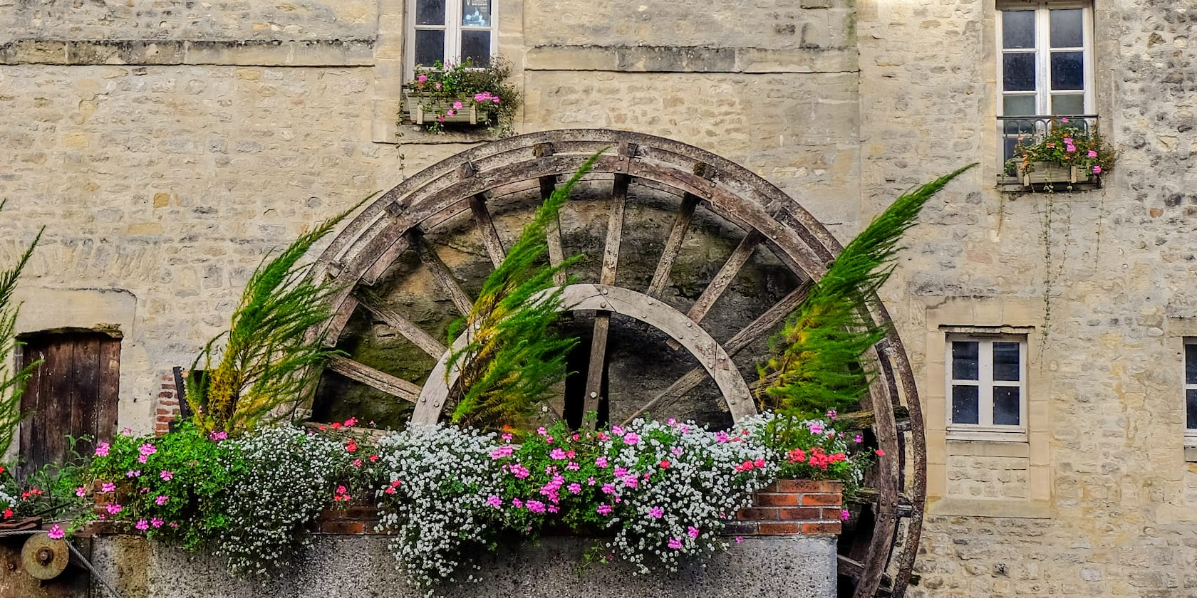 Plants and flowers in a planter in front of a mill wheel that is next to an old brick building