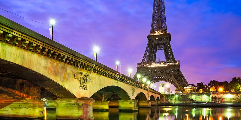 A bridge spans the Seine River with the Eiffel Tower at dusk