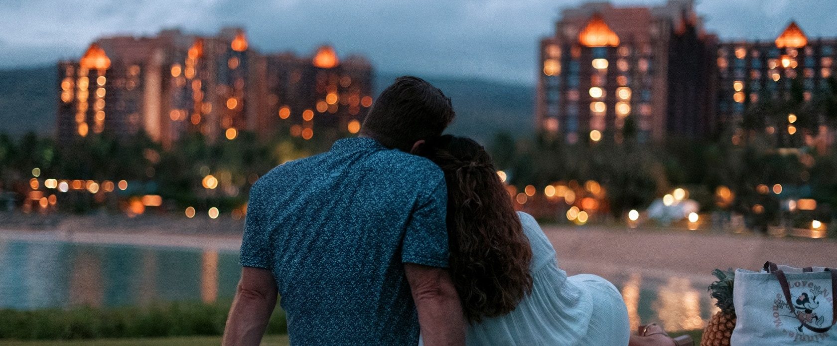 A couple cuddle up next to each other on a grassy area overlooking Aulani Resort A Disney Resort and a Spa in Hawaii