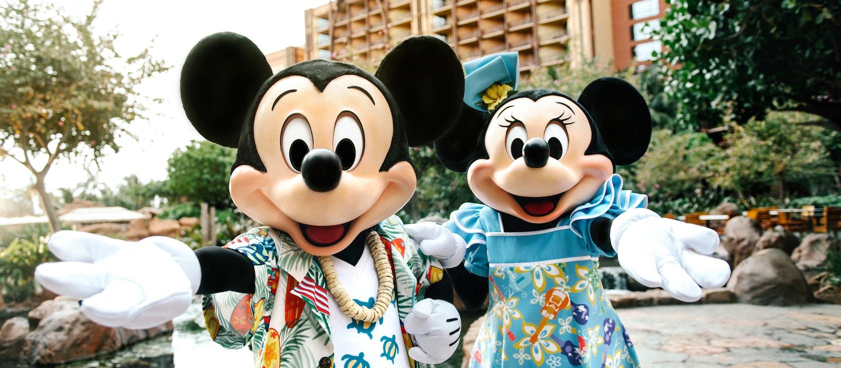 ハワイアンスタイルの衣装を着て、手を差し出してゲストを迎えるミッキーとミニー