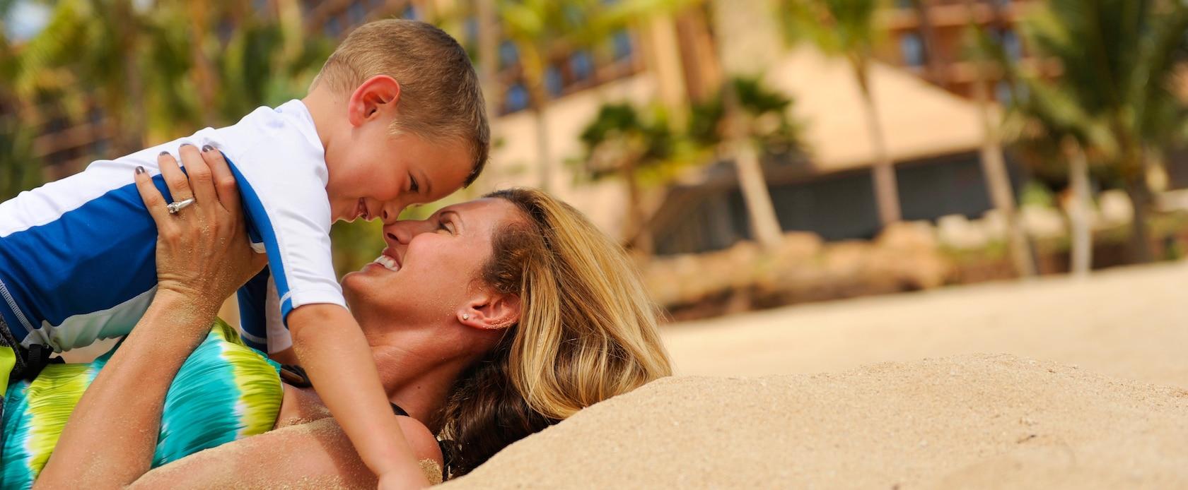 ビーチに仰向けになり、抱っこした小さな息子の鼻に自分の鼻をつけて微笑む母親