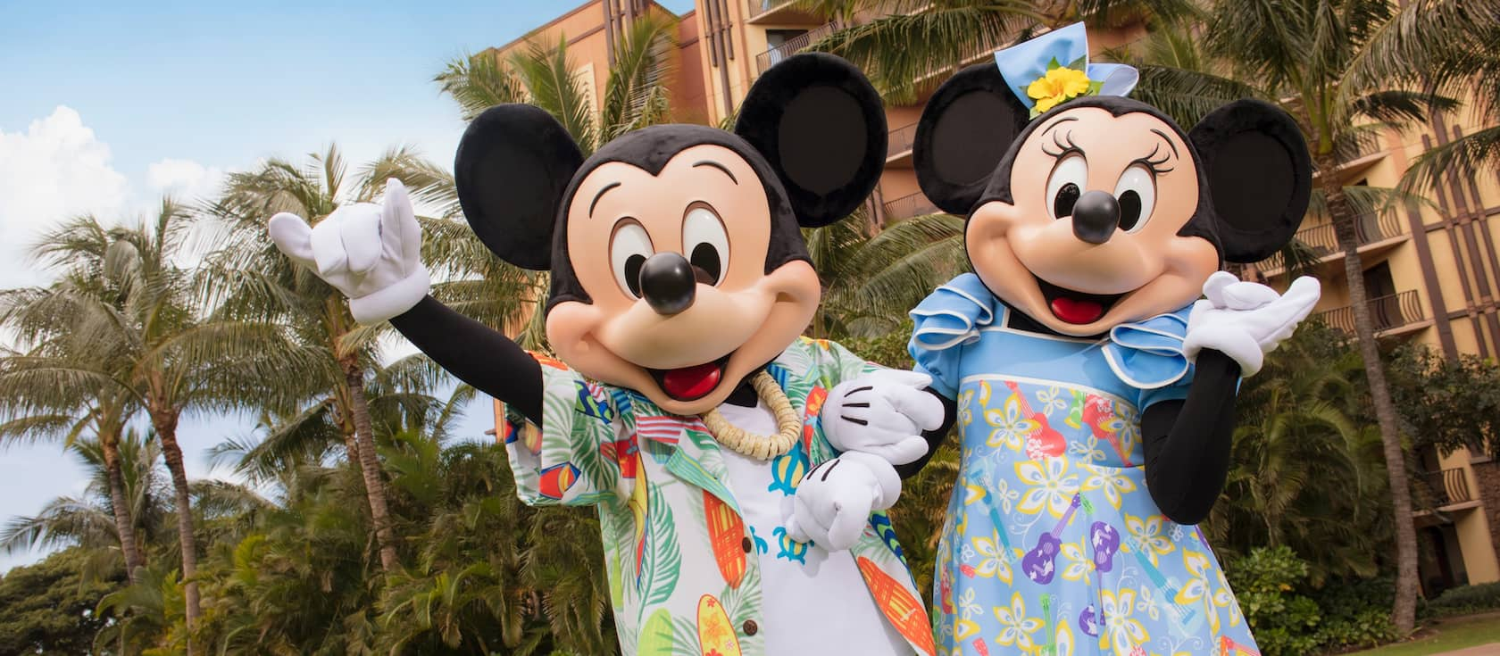 Mickey Mouse and Minnie Mouse, dressed in Hawaiian style outfits, stand in front of a wing of Aulani Resort