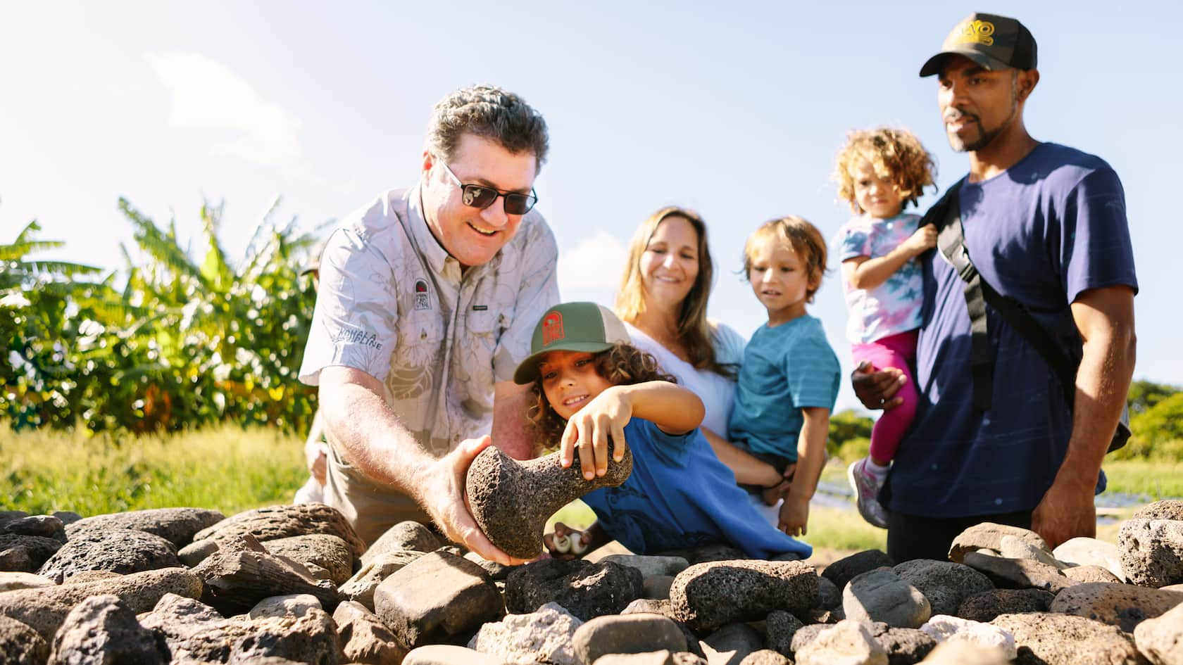 Adults and kids look at a pile of rocks, fascinated by a lava rock with a distinctive shape