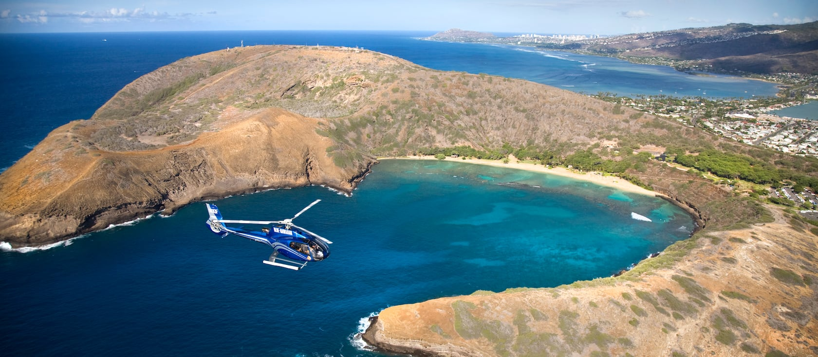A helicopter flies over Hanauma Bay on the island of Oahu in the Hawaiian Islands