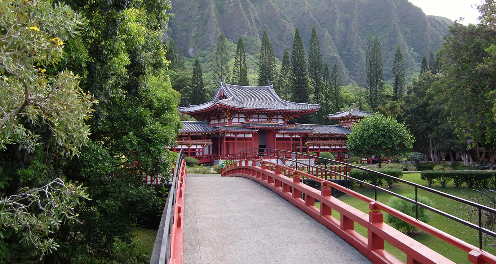 A wooden bridge leading to a temple situated in a verdant valley