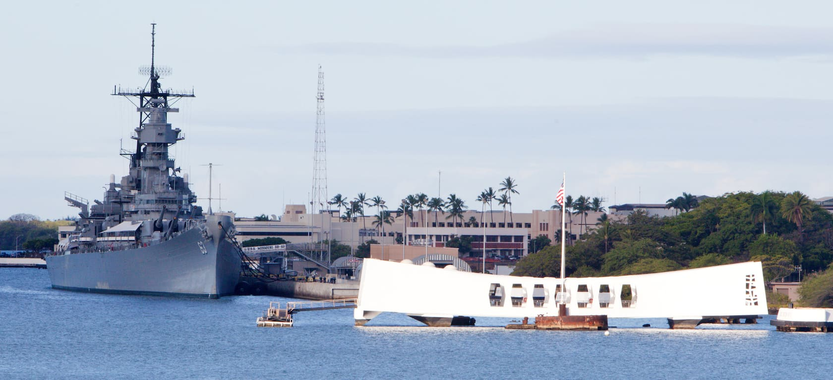 At Pearl Harbor, Hawaii, the broad geometric U S S Arizona Memorial is situated in the water beside the battleship U S S Missouri, which is docked at the pier