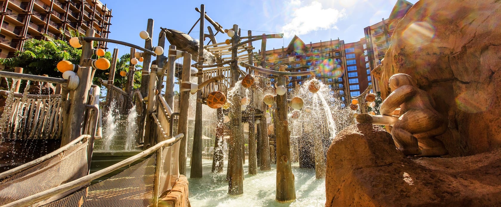 Water spills down from the Menehune Bridge as the Resort's rooms and suites tower in the background