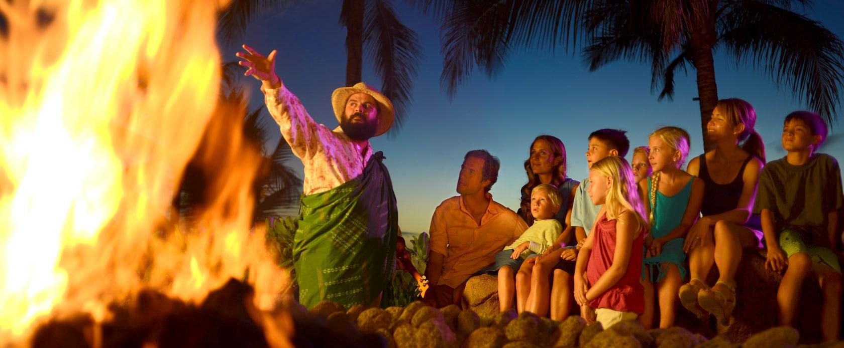 帽子をかぶりサロンを身に着けた男性が、燃え盛る炎に向かってドラマチックな身振りで語り、それを見つめる子供たちと両親