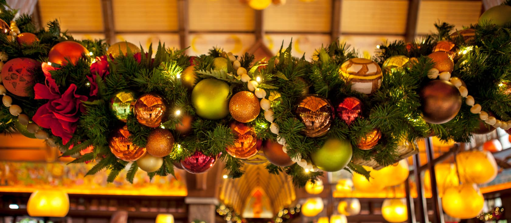 An evergreen Christmas swag decorated with ornaments and strung with beads hanging in the Aulani Resort lobby