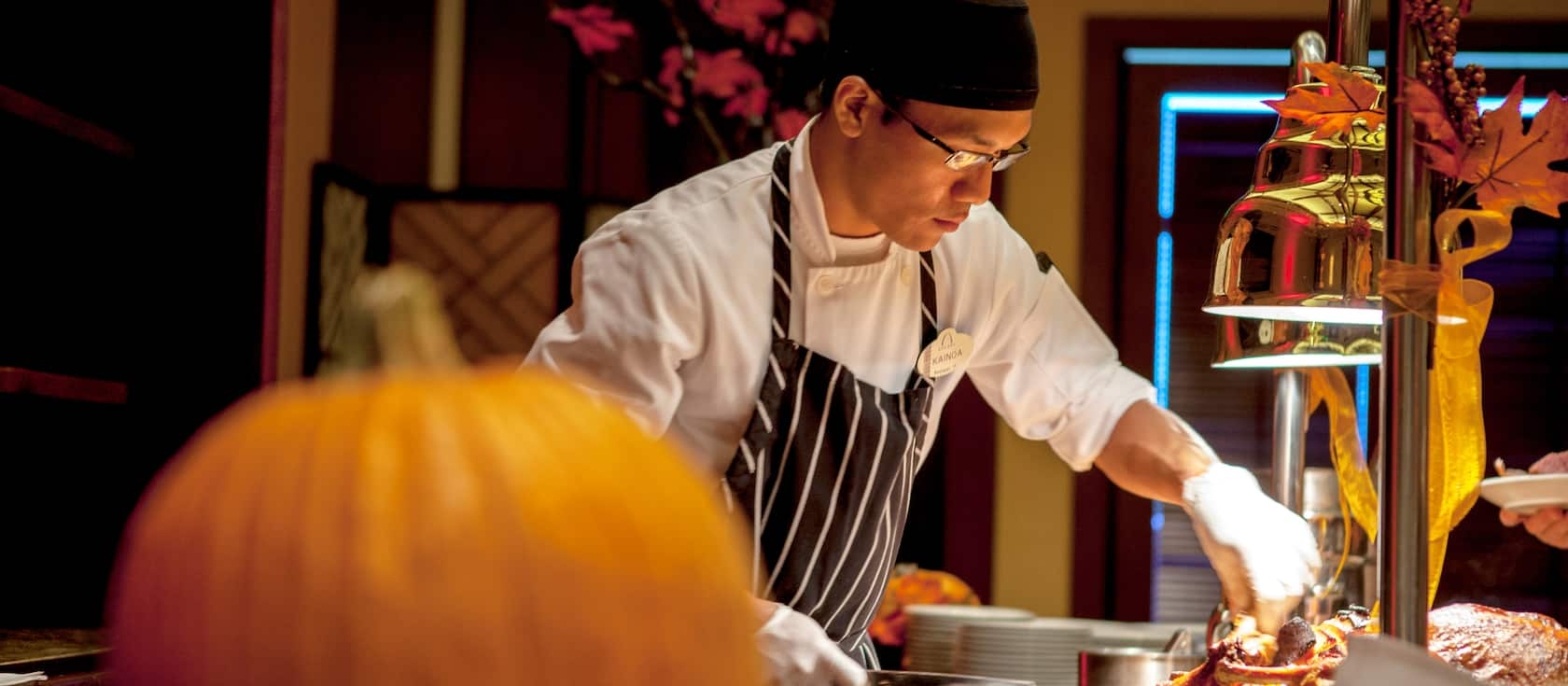 A chef wearing an apron and bandana puts the finishing touches on a dish at a serving station decorated with Thanksgiving décor that includes a pumpkin