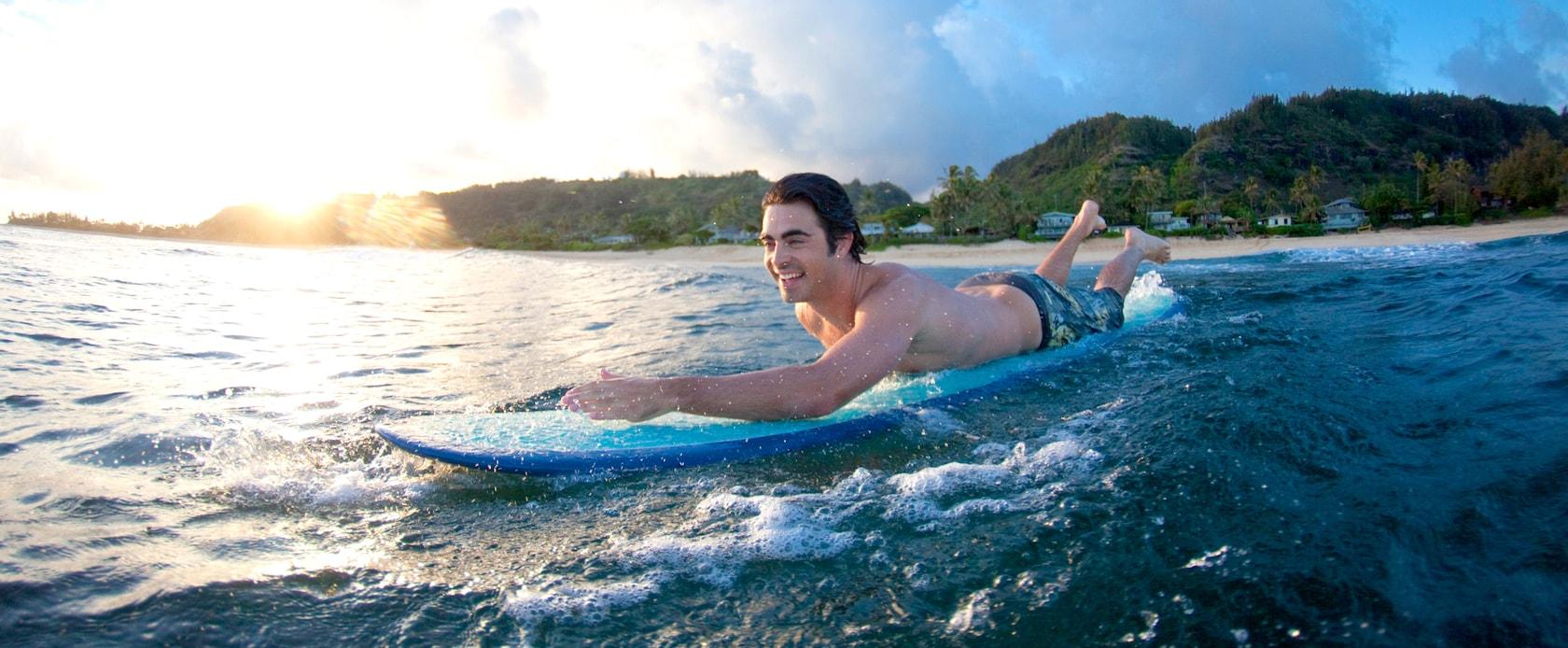 サーフボードに乗り海に出る若い男性、その向こうには木に覆われた丘のある海岸線がひろがります