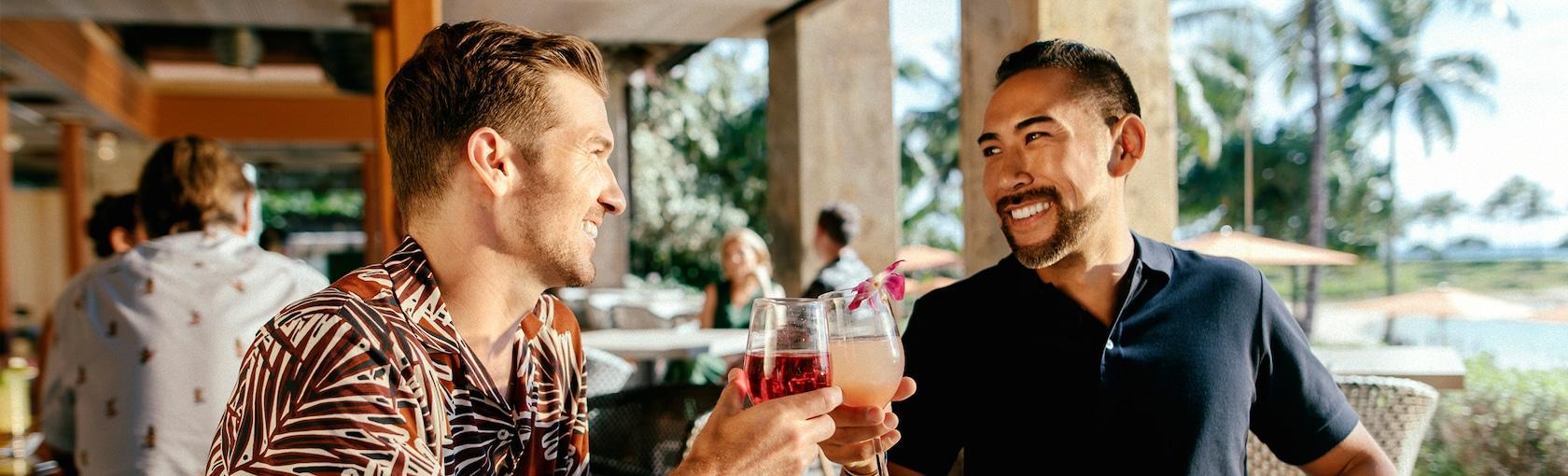 パティオのテーブルで笑顔でグラスを傾ける 2 人の若い男性