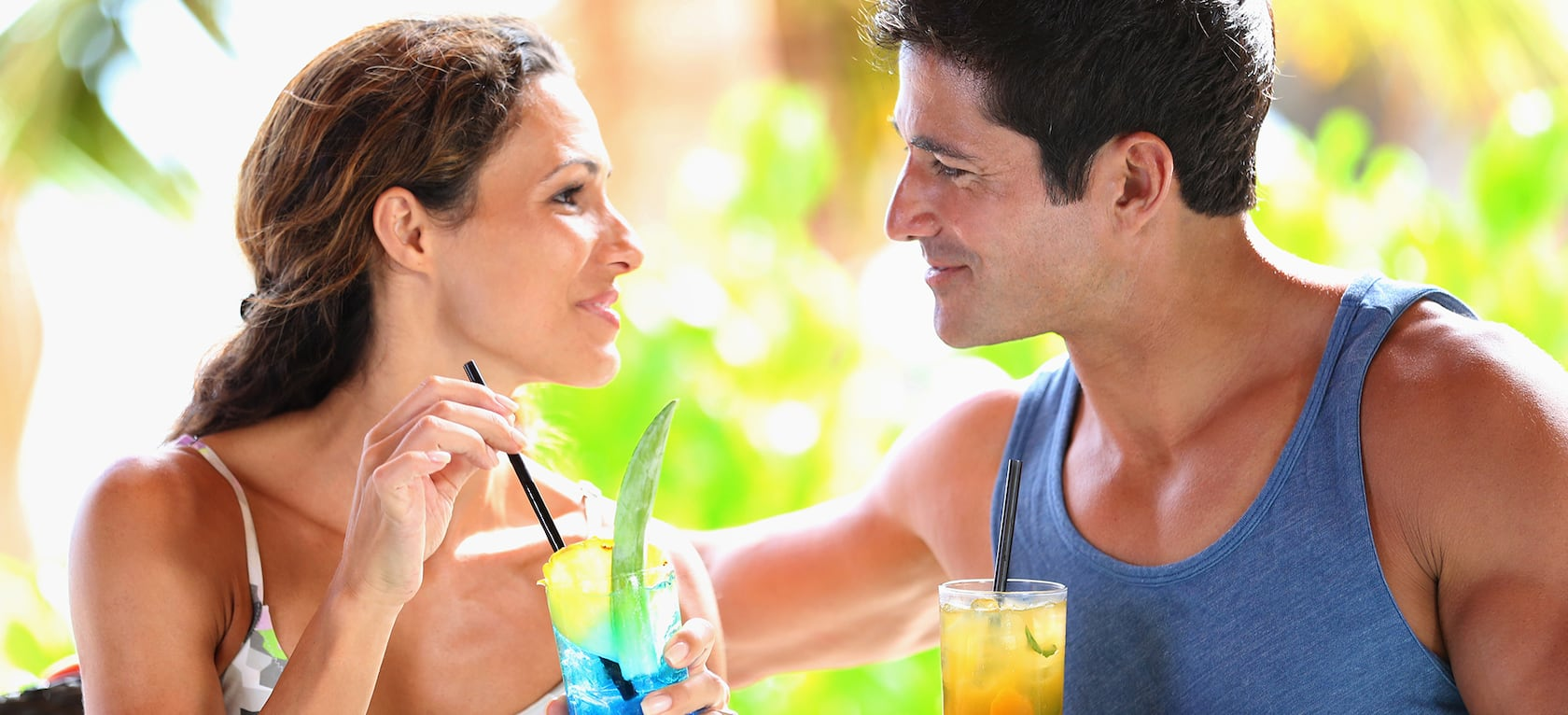 A woman and a man gaze into each other's eyes while enjoying cocktails