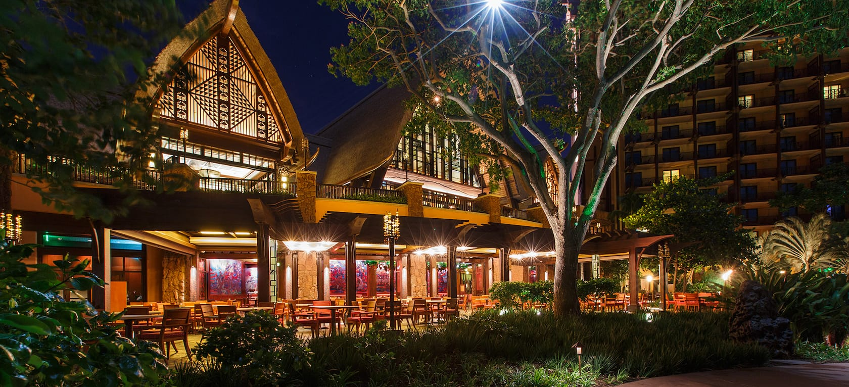 The exterior of Makahiki at night, with a lit-up covered patio and twin peaked roofs with native designs