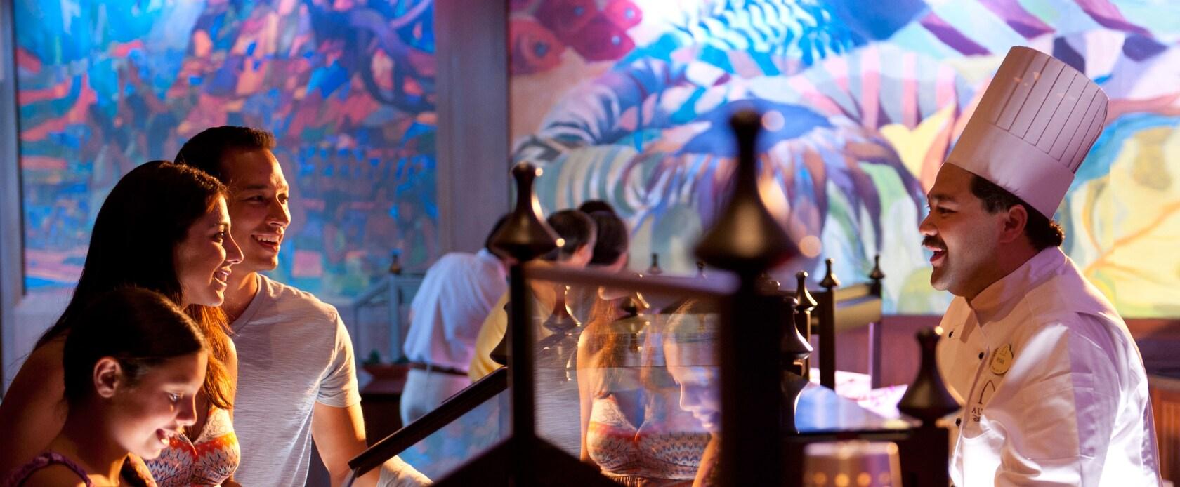 温かい食事とカービング・ステーション、上部にカラフルに描かれた壁画のあるビュッフェ