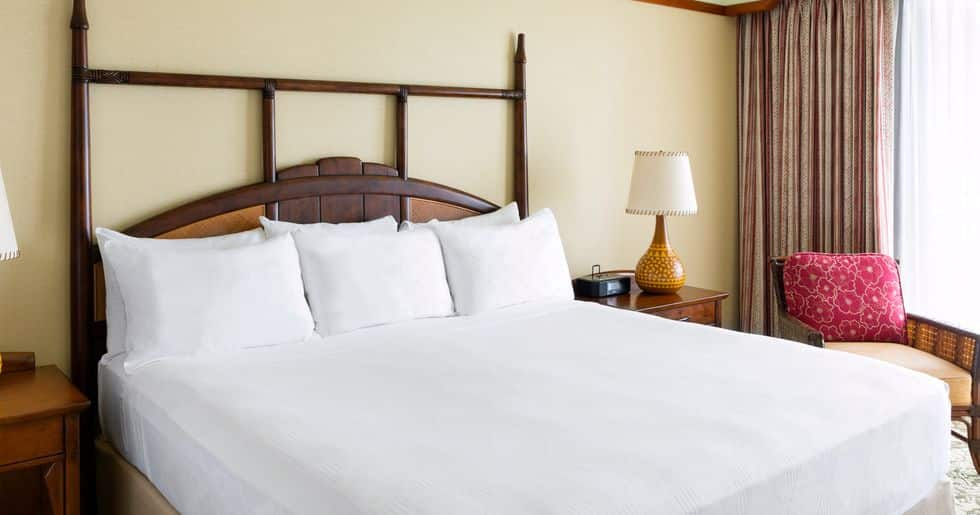 キングサイズのベッドと向かいに置かれた薄型テレビ、ガラス戸の向こうに見えるバルコニー