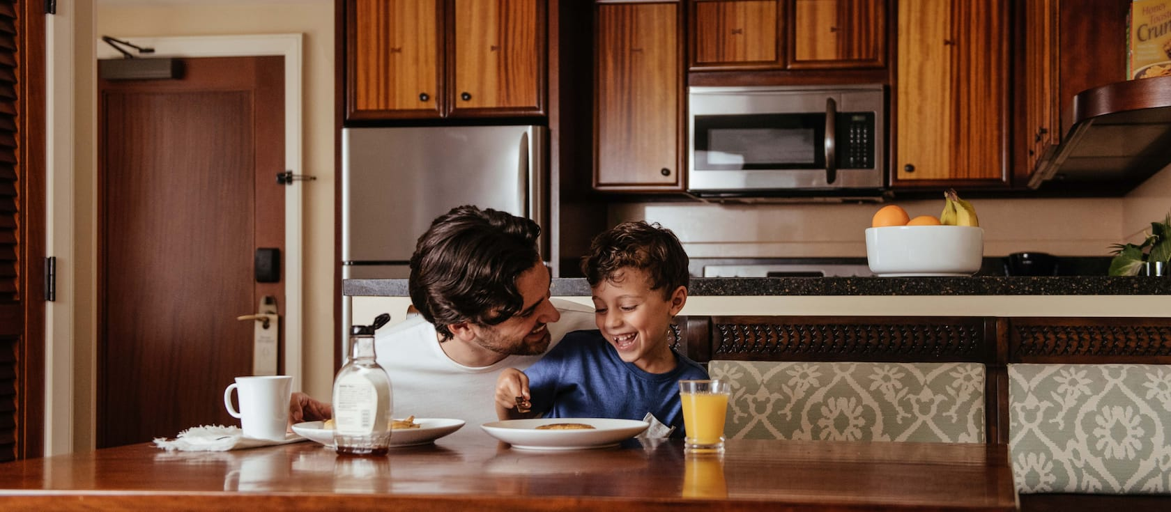 A father and son laugh as they eat pancakes at a kitchen table