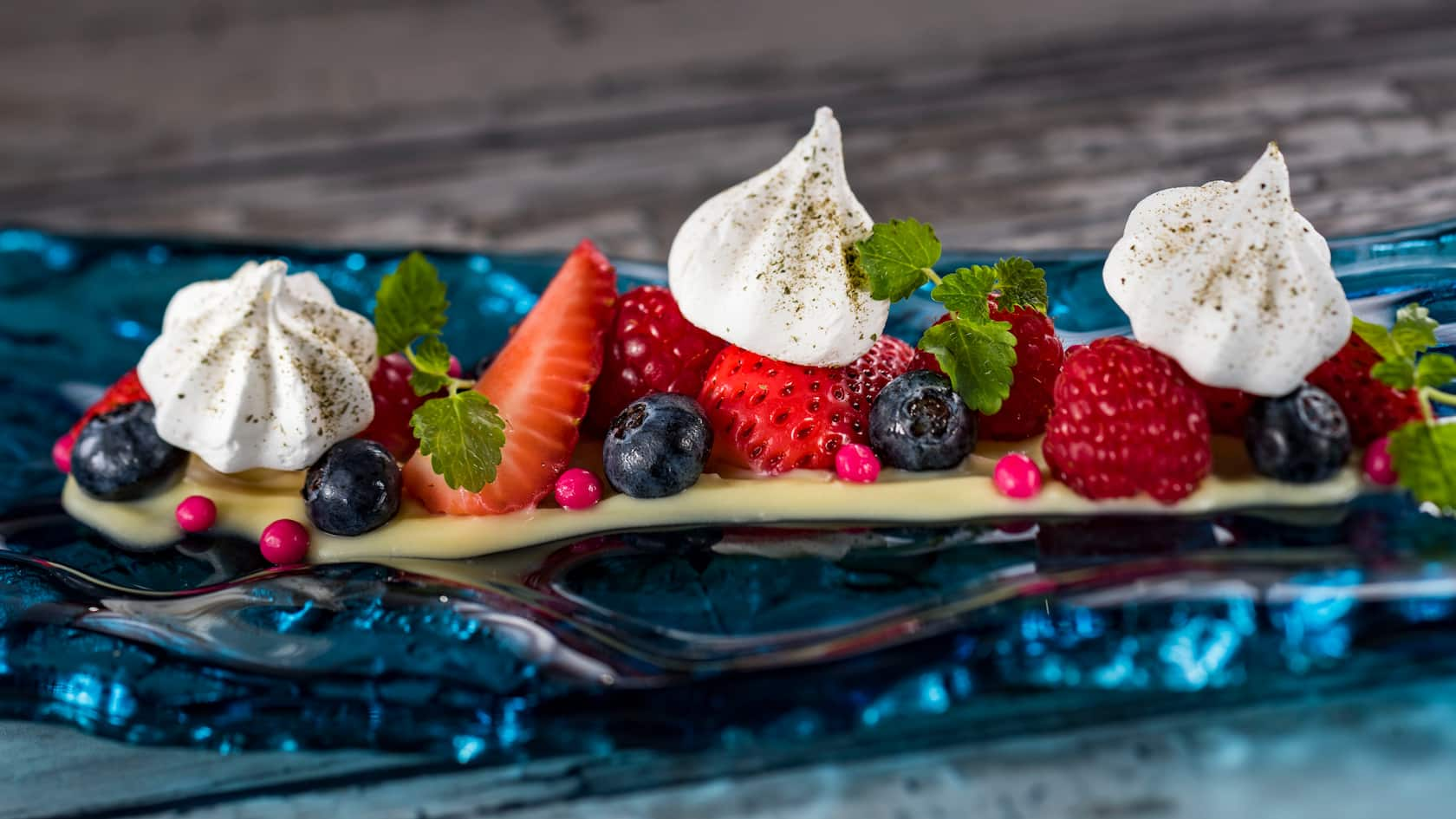 Strawberries, raspberries, blueberries and cranberries artfully arrange on a decorative plate with cream and herbs