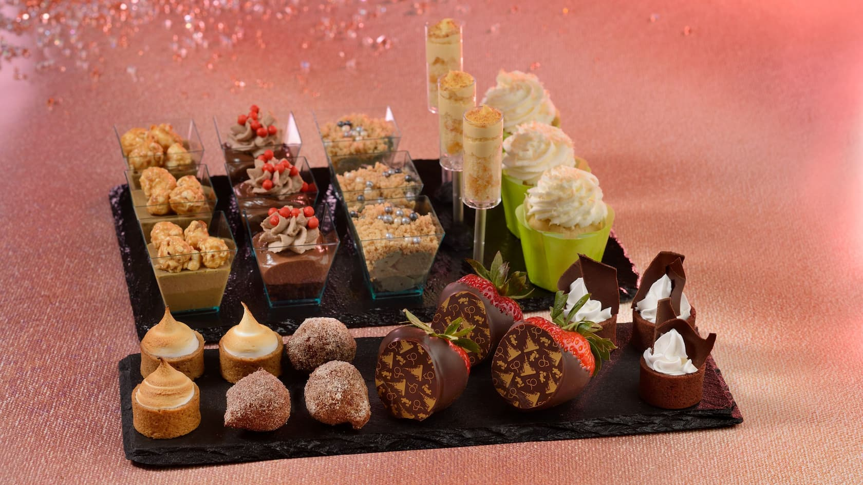 Trays holding 9 different desserts, including chocolate-covered strawberries, butterscotch pudding and pastries