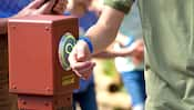 A Guest puts his MagicBand up to a touchpoint in a Disney Park